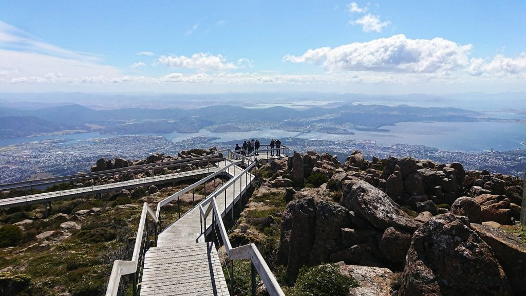 Visitors enjoying the spectacular views from a lookout on the summit of kunanyi/Mt Wellington.