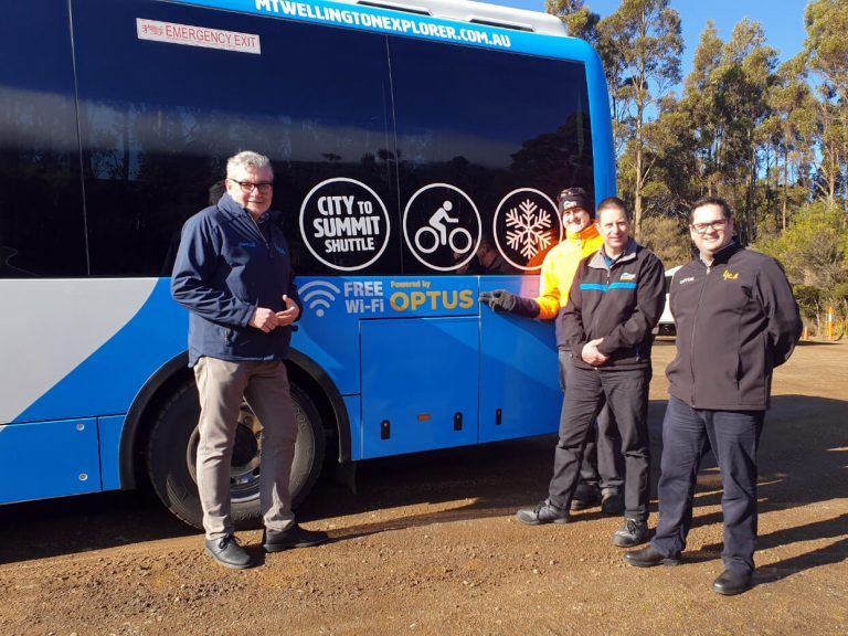 kunanyi/Mt Wellington Explorer Bus and Optus staff members standing next to the Mt Wellington bus.