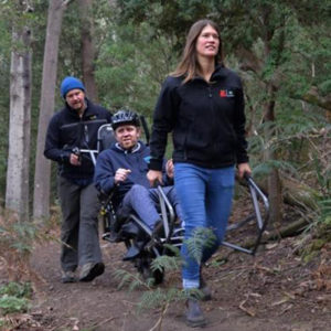 Man sitting in an accessible bushwalking wheelchair, assisted by 2 people walking through the bush.