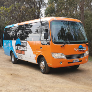 An orange and blue bus sits on a dirt road with trees in the background.