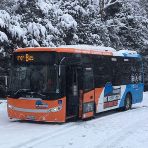 An orange and blue bus sits in the snow.